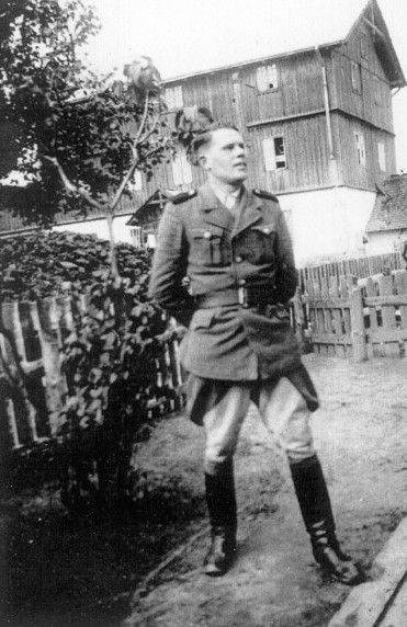 An SS man on the staff of the Belzec camp, posing in front of the flour mill used as an assembly place for Jews deported to the camp.